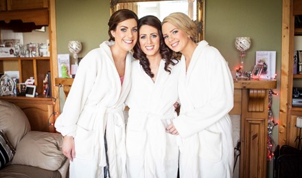 Bride and 2 bridesmaids in their wedding robes. hair and makeup complete Makeup artist finished. Beautiful , stunning makeup and bridal party.