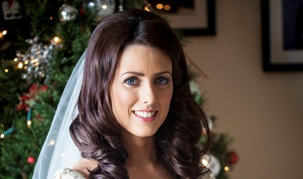 bride beside a christmass tree holding her  wedding flowers bridal hair and make up done. beautiful jewelry posing for her photographer.
